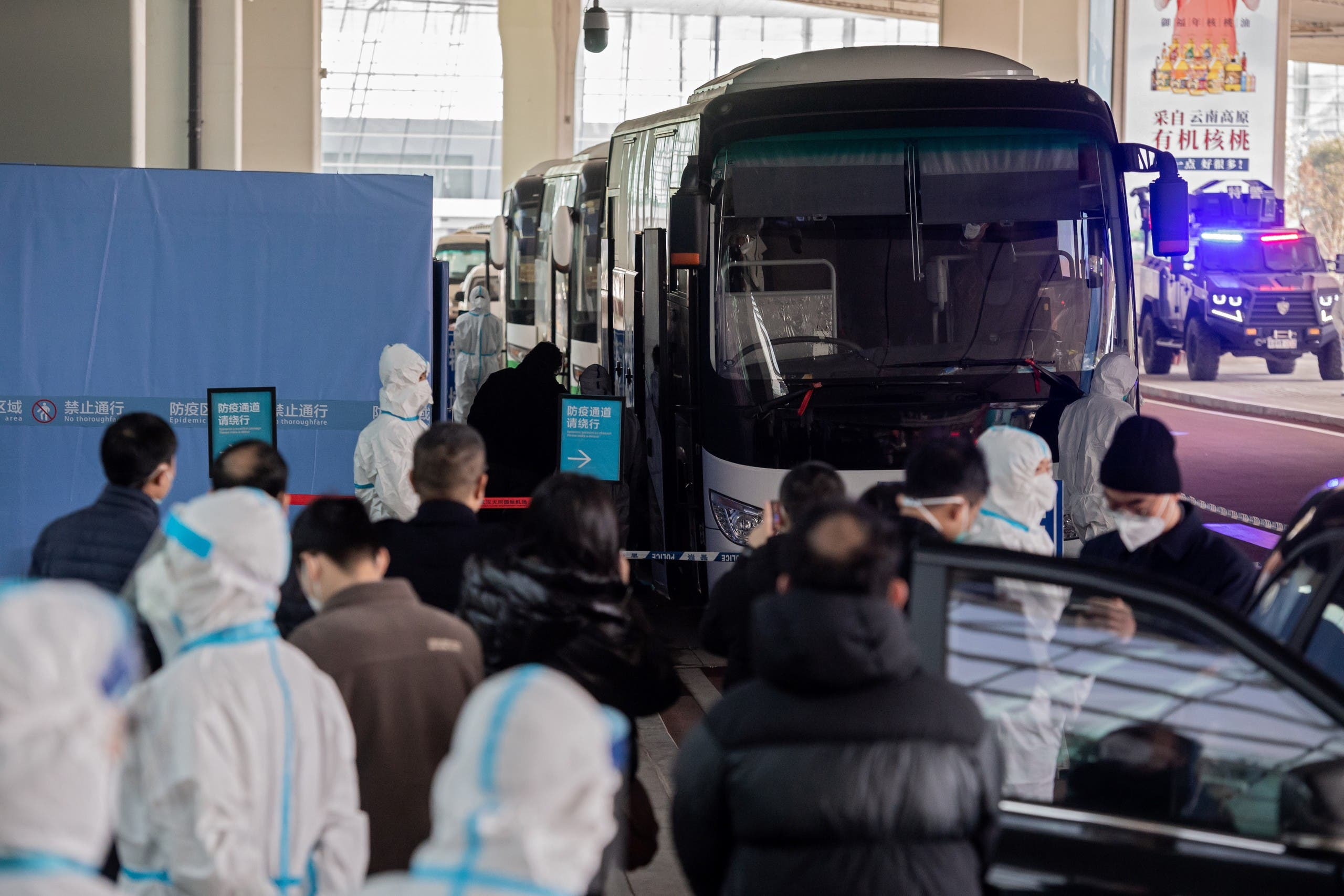 Members of the World Health Organization (WHO) team investigating the origins of the Covid-19 pandemic board a bus following their arrival at Wuhan. (AFP)