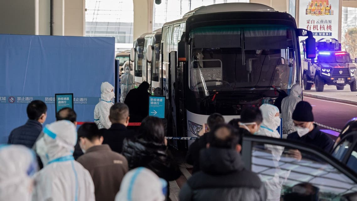 Members of the World Health Organization (WHO) team investigating the origins of the Covid-19 pandemic board a bus following their arrival at a cordoned-off section in the international arrivals area at the airport in Wuhan. (AFP)