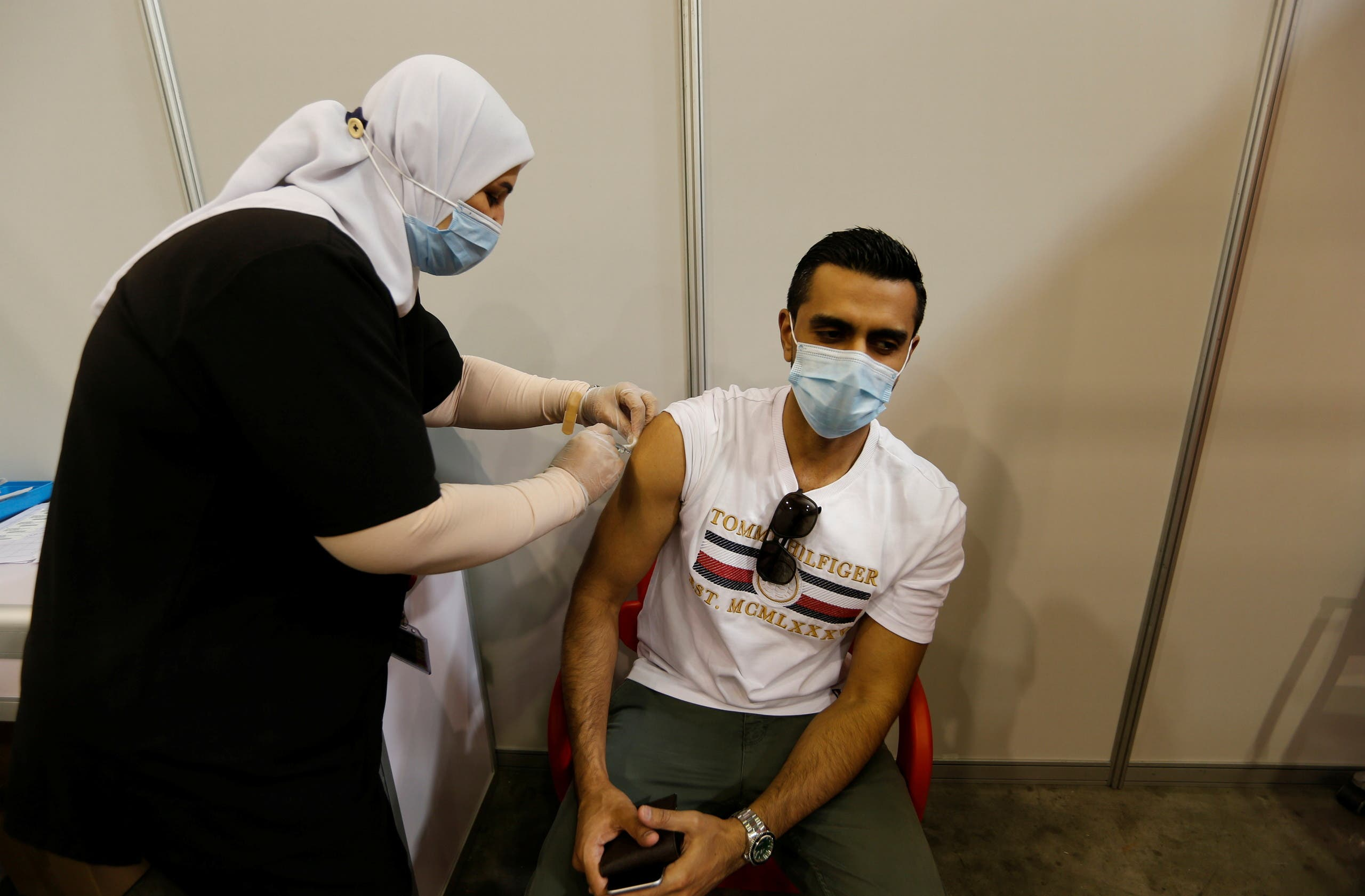 A Bahraini man gets a dose of a coronavirus disease (COVID-19) vaccine, at Bahrain International Exhibition & Convention Centre (BIECC), in Manama. (Reuters)