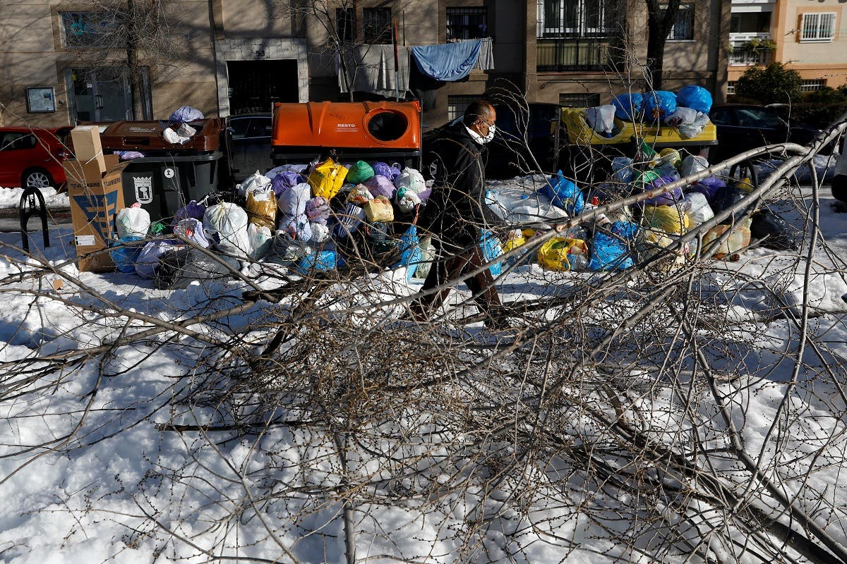 A man walks past accumulated garbage and broken tree branches after heavy snowfall in Madrid. (Reuters)