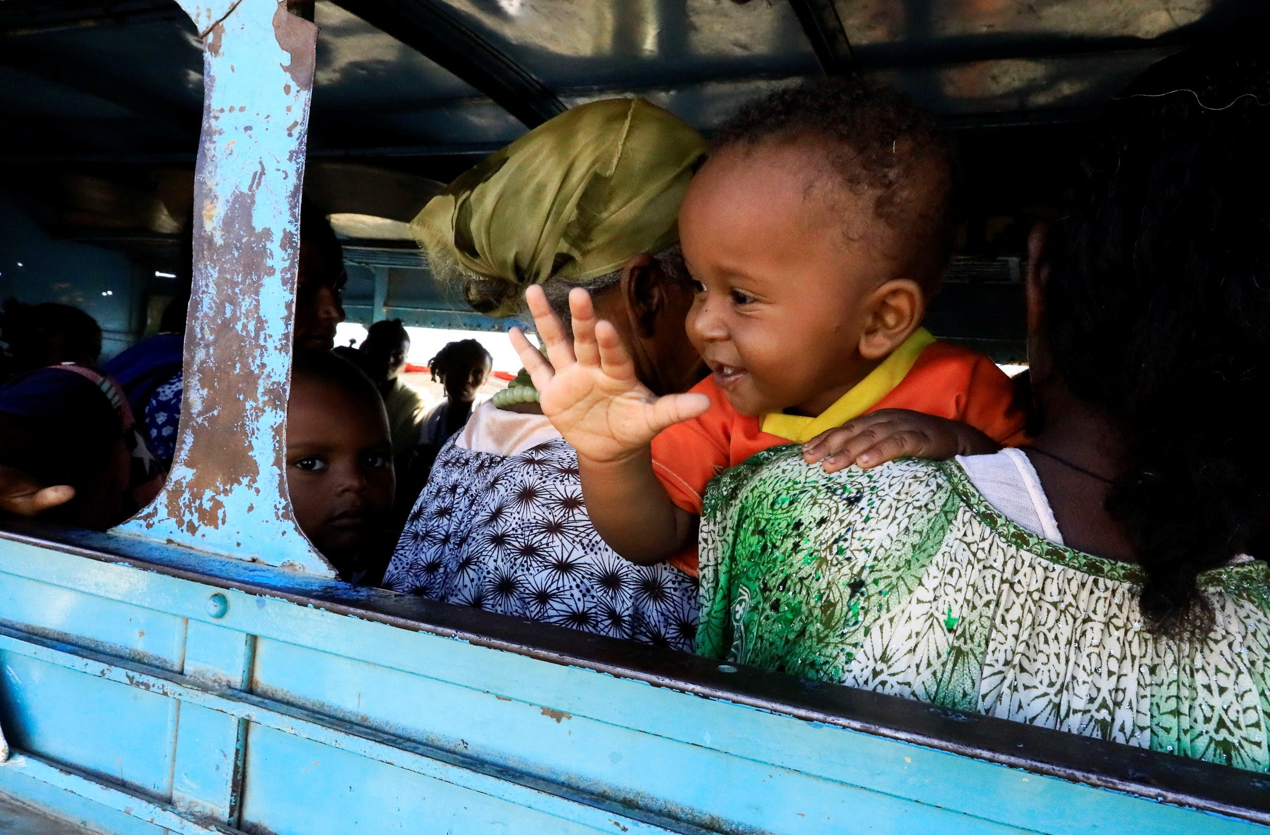 An Ethiopian refugee who fled Tigray region holds a child inside a courtesy bus at the Fashaga camp, as they are transferred to Um-Rakoba camp on the Sudan-Ethiopia border, in Kassala state, Sudan. (Reuters)