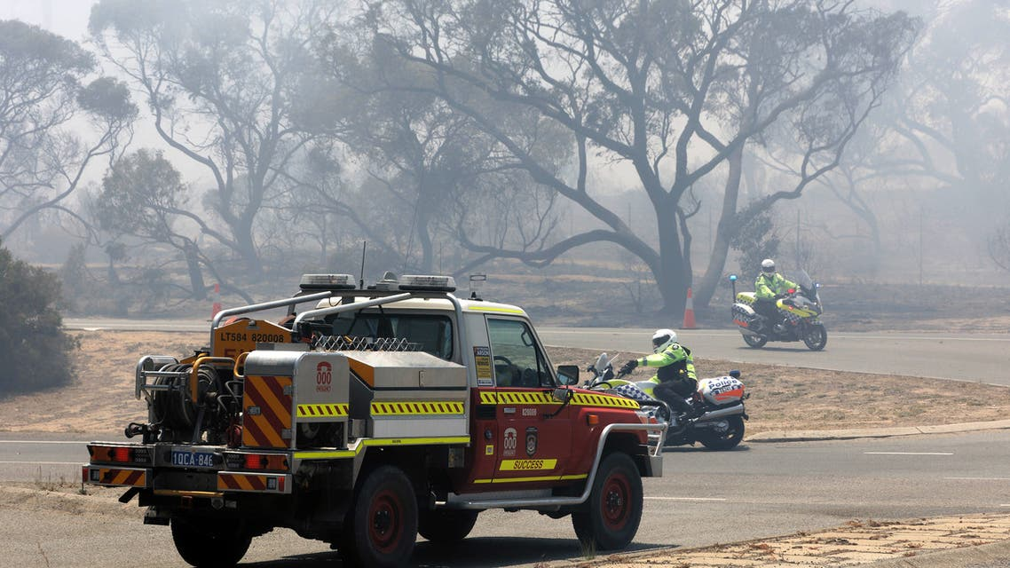 Emergency vehicles patrol the perimeter while battling a bush fire in Kwinana, some 30 kilometres south of Perth on January 4, 2021. TREVOR COLLENS / AFP
