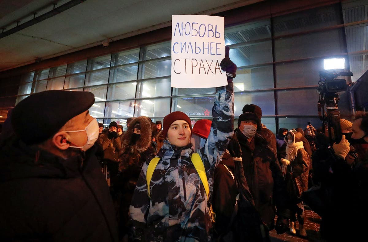 An activist holds a placard which reads: Love is stronger than fear, outside a terminal before the arrival of Russian opposition leader Alexei Navalny at Vnukovo International Airport in Moscow, Russia January 17, 2021. (Reuters)