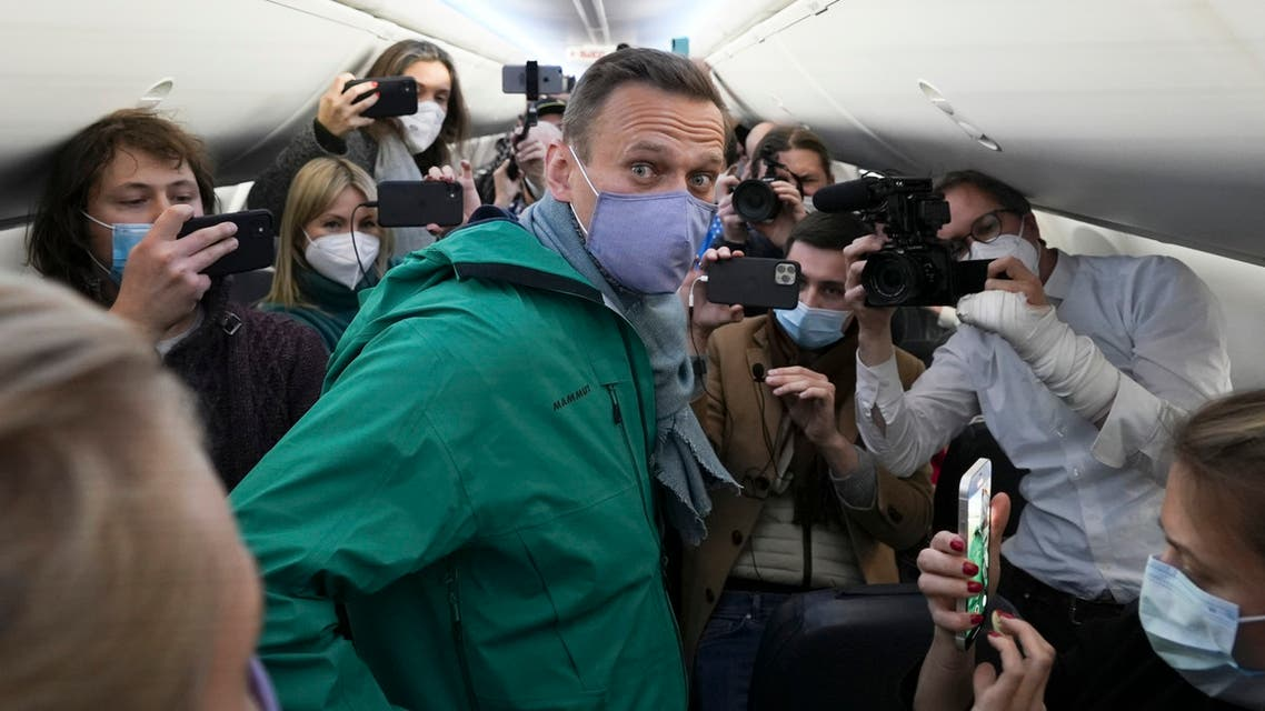 Alexei Navalny is surrounded by journalists inside the plane prior to his flight to Moscow in the Airport Berlin Brandenburg (BER) in Schoenefeld, near Berlin, Germany, Sunday, Jan. 17, 2021. Leading Kremlin critic Alexei Navalny plans to fly home to Russia on Sunday after recovering in Germany from his poisoning in August with a nerve agent. (AP Photo/Mstyslav Chernov)