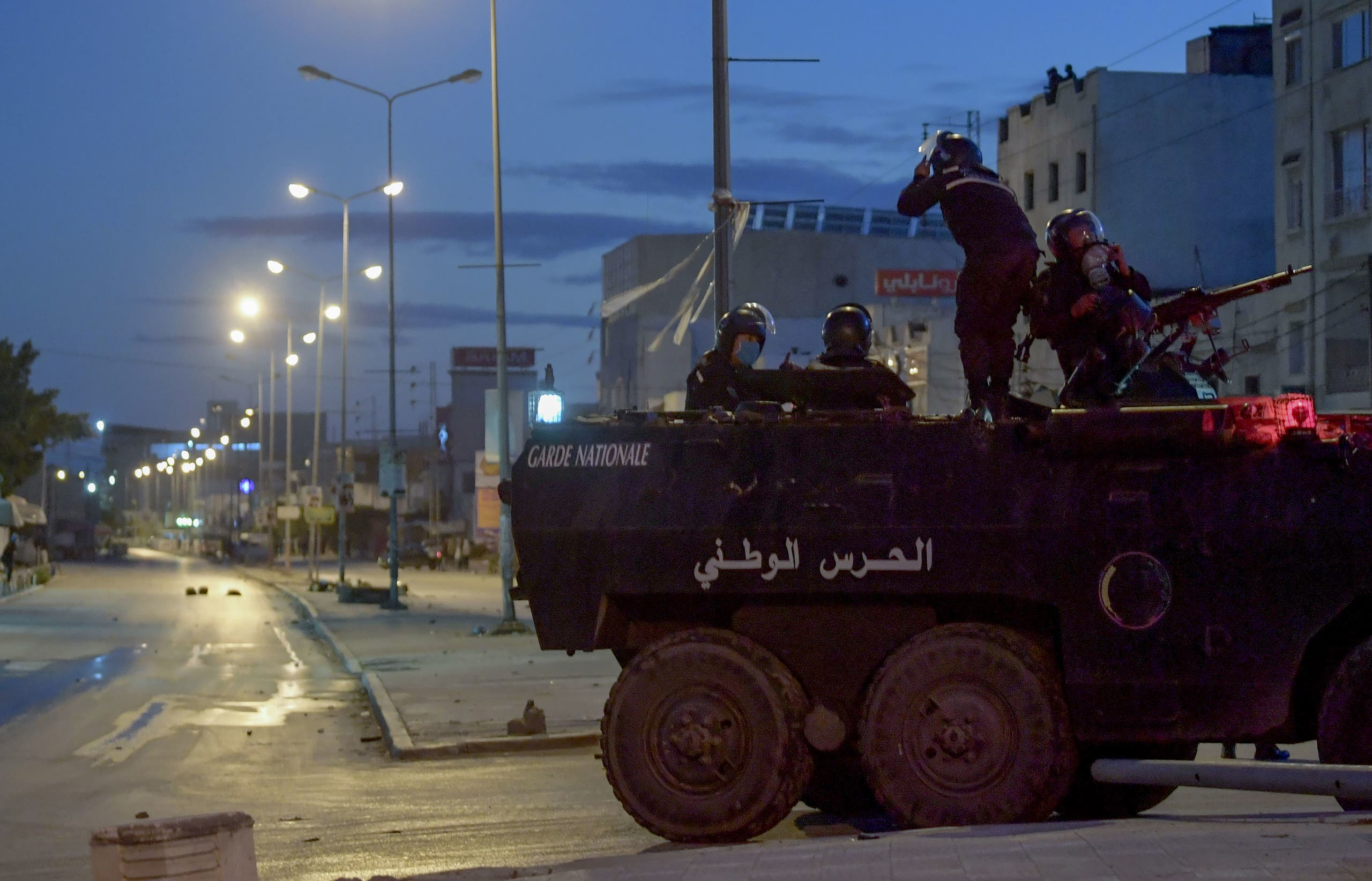 Members of the Tunisian National Guard sit atop their armoured vehicle, stationed on a street amid clashes with demonstrators following a protest in the Ettadhamen neighbourhood in the capital Tunis, on January 17, 2021. (AFP)