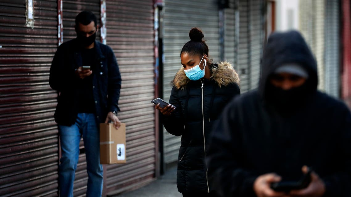 People look at their mobile phones as they walk past closed shops in London on Jan. 16, 2021. (AP)