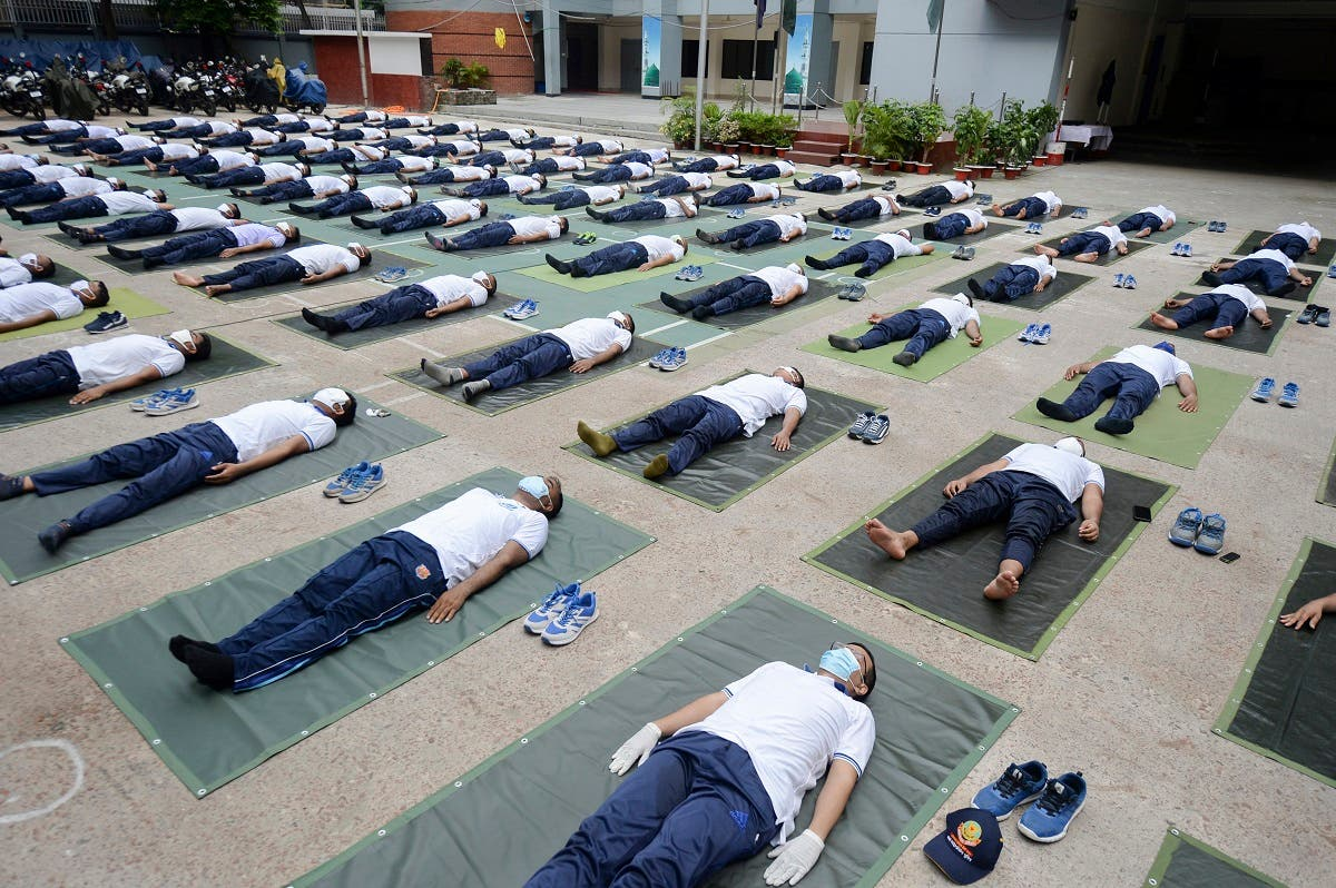 Members of the Bangladesh police attend a yoga session to boost the immune system of police personnel during the COVID-19 coronavirus pandemic, in Dhaka on June 8, 2020. (Munir Uzzaman/AFP)