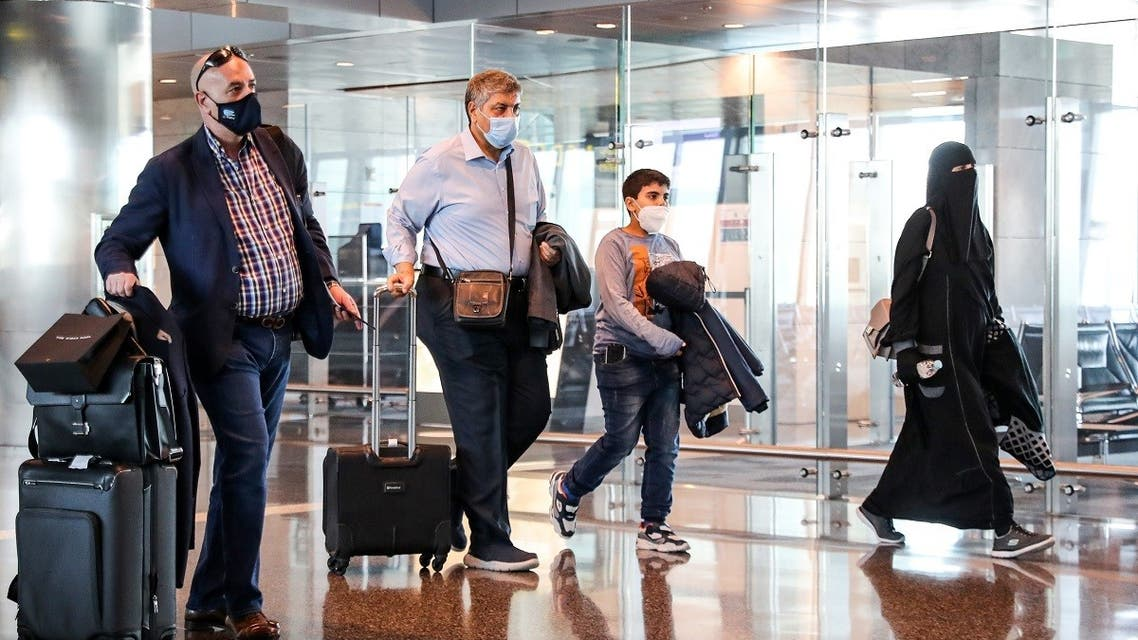 Mask-clad travelers walk with their carry-on luggage to board the first Qatar Airways flight bound for Cairo after the resumption of flights between Qatar and Egypt, at Qatar's Hamad International Airport near the capital Doha on January 18, 2021. (Karim Jaafar/AFP)