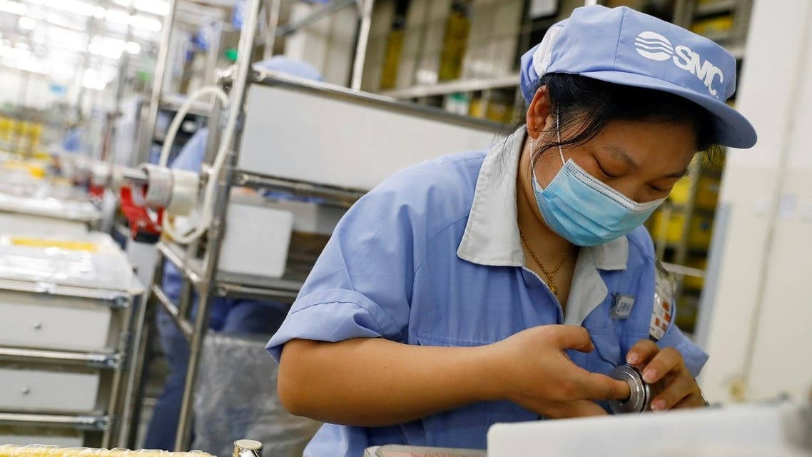 An employee wearing a face mask works at a factory of the component maker SMC during a government organized tour of its facility following the outbreak of the coronavirus in Beijing, China, on May 13, 2020. (Reuters)