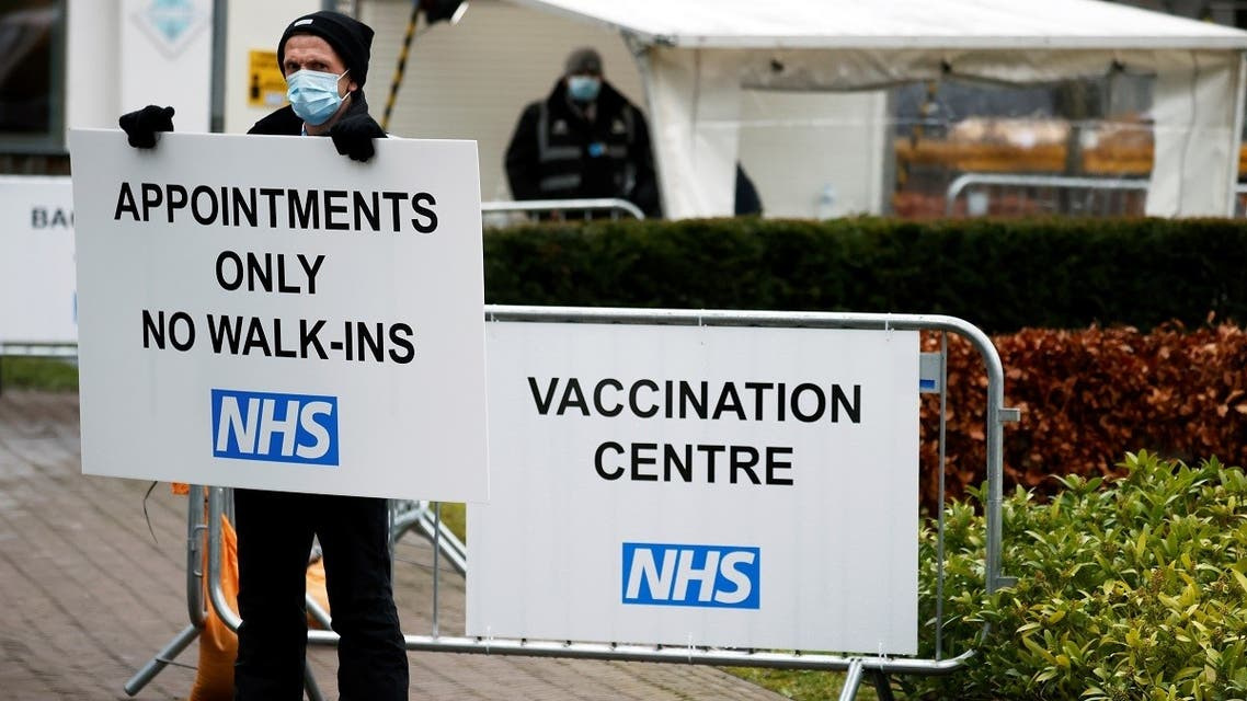 A worker holds an information sign at the entrance of Blackburn Cathedral, ahead of its opening as a vaccination center for the coronavirus, in Blackburn, Britain, January 18, 2021. (Reuters/Phil Noble)