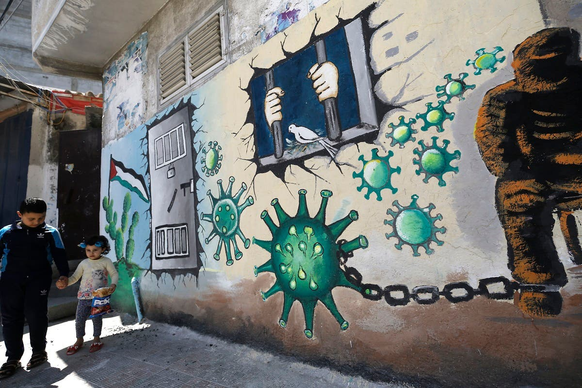 Palestinian children walk past a mural depicting the coronavirus and a prison cell, in Gaza City during the coronavirus pandemic on April 28, 2020. (Mohammed Abed/AFP)