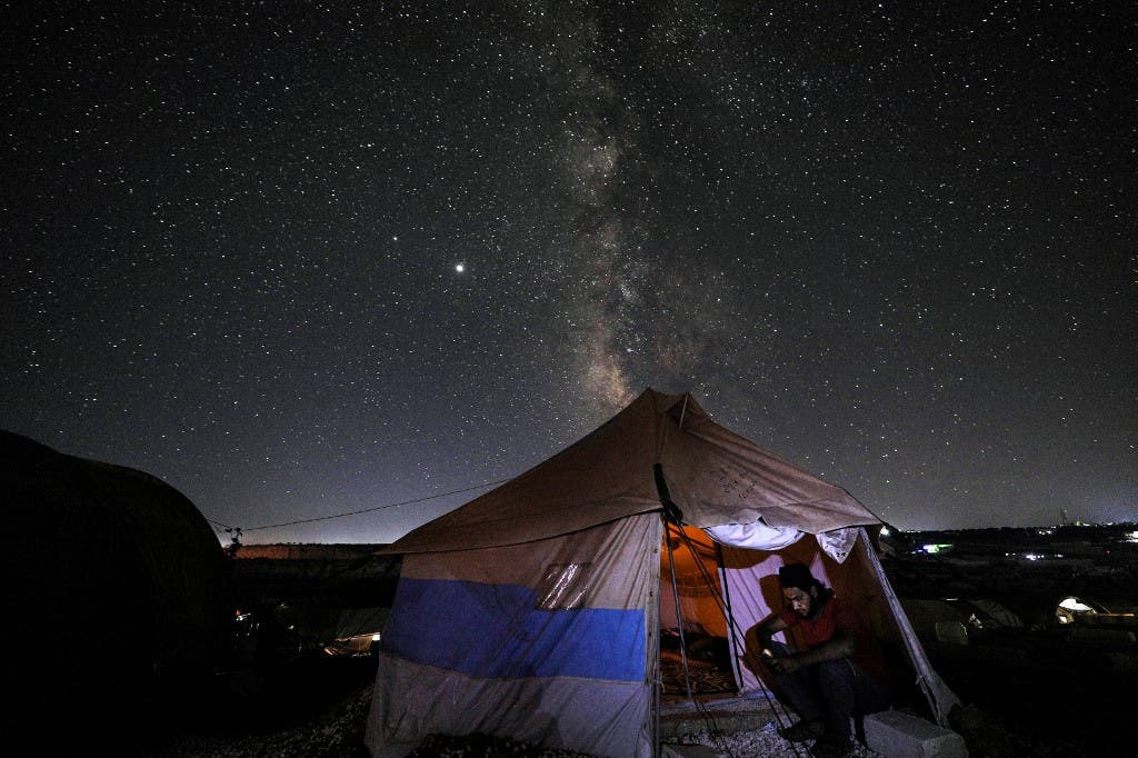 This long-exposure picture taken early on July 20, 2020, shows a man browsing a phone while seated at the entrance of a tent as the Milky Way galaxy rises in the sky above the Ahl al-Tah camp for displaced persons near the town of Maaret Misrin in Syria's northwestern Idlib province. (AFP)