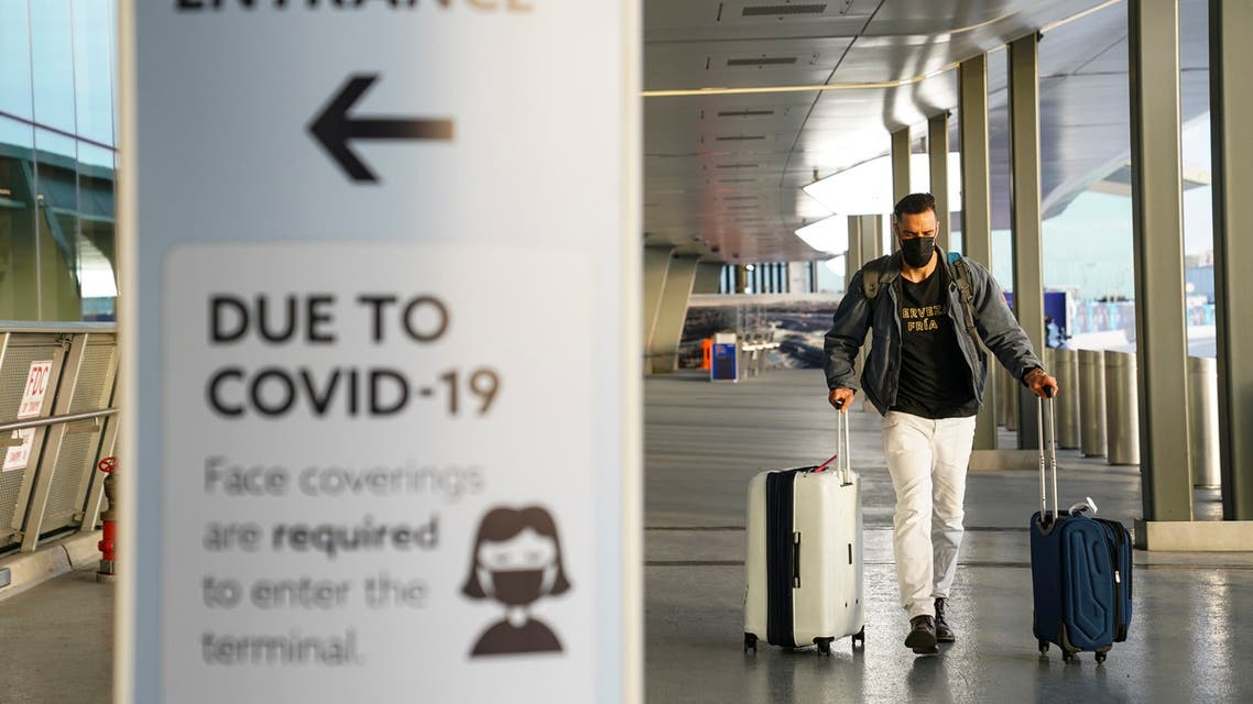 A sign displaying COVID-19 prevention protocols stands beside the passenger drop-off area as travelers arrive at Terminal C at LaGuardia Airport. (AP)