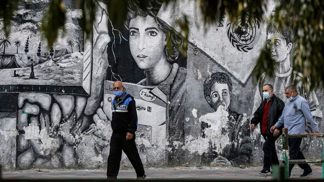 Palestinians, mask-clad due to the COVID-19 coronavirus pandemic, walk past a mural about Palestinian refugees drawn on a wall along a street in Gaza City on November 8, 2020. (Mohammed Abed/AFP)
