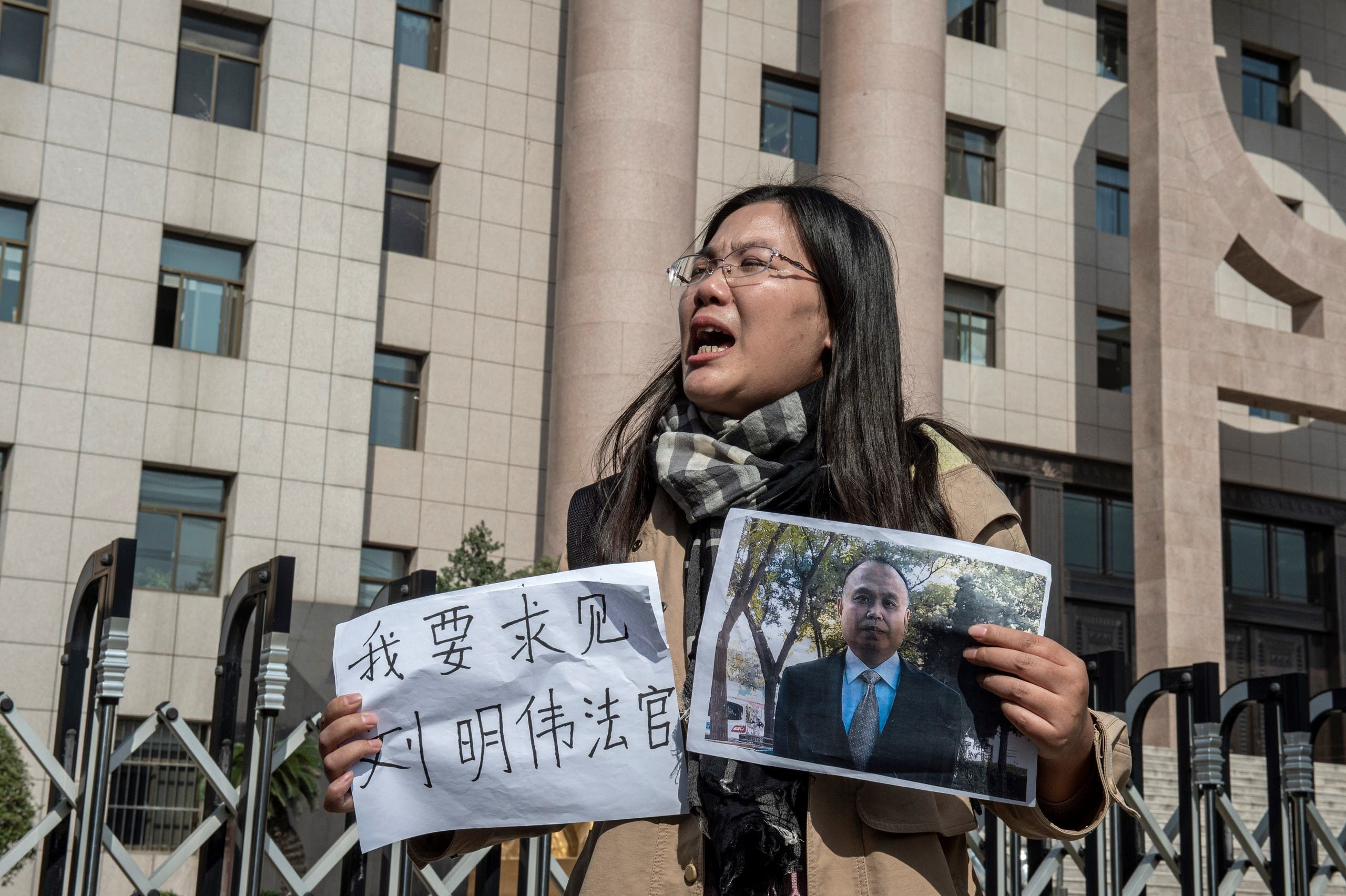 Xu Yan, wife of human rights lawyer Yu Wensheng, holding a piece of paper that reads 'I want to request a meeting with Judge Liu Mingwei' and a picture of her husband outside the Xuzhou Intermediate People's Court in Xuzhou on October 31, 2019. (AFP)