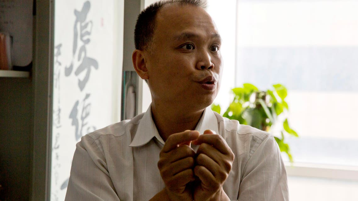 In this Thursday, July 23, 2015 photo, Chinese lawyer Yu Wensheng holds up his hands to show how death row prisoners are handcuffed 24 hours a day during an interview at his office in Beijing. Chinese lawyer who spoke up on behalf of rights lawyers persecuted by authorities was himself taken away by police in handcuffs, his wife said Friday, Aug. 7. (AP Photo/Ng Han Guan)