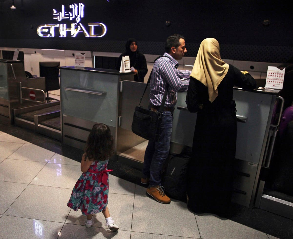 A file photo shows passengers check into a flight at Abu Dhabi International Airport in Abu Dhabi, United Arab Emirates, July 4, 2017. (AP/Jon Gambrell)
