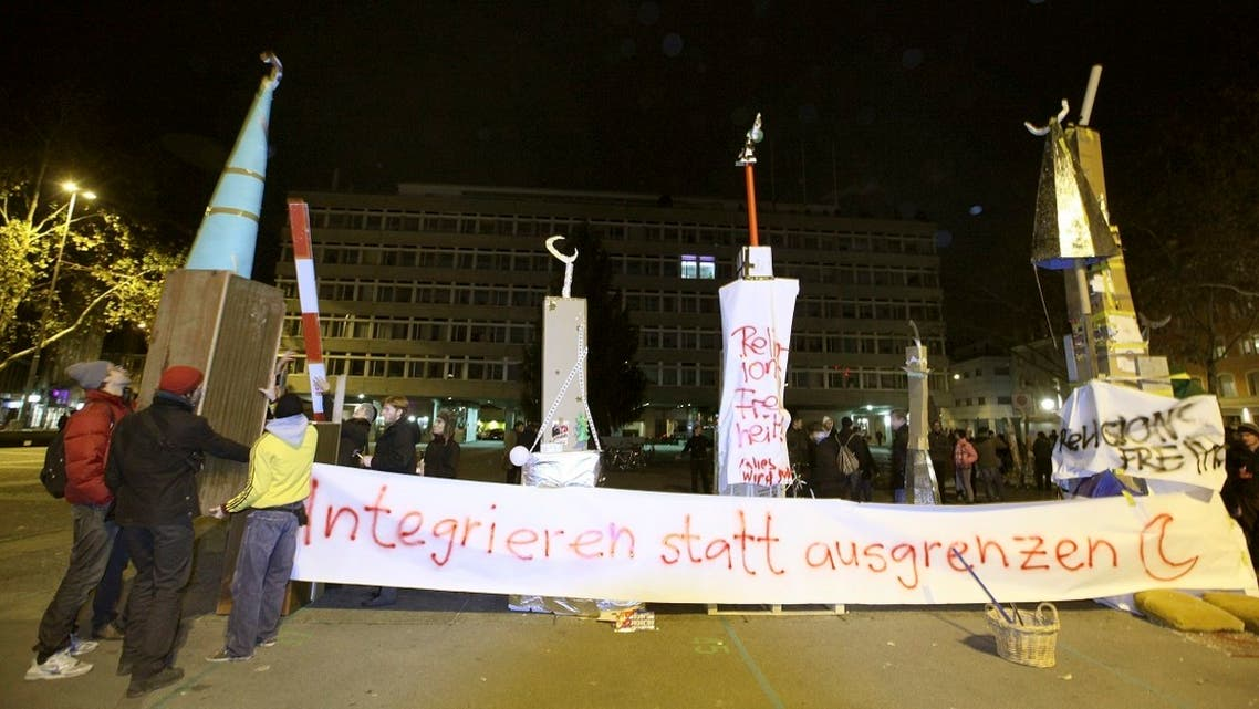 Protesters erect symbolic minarets to protest against the results of a vote in Switzerland at the Helvetiaplatz square in Zurich, on November 29, 2009. Switzerland voted to ban the construction of new minarets. The banner reads 'Integrate instead of segregate.' (Reuters)