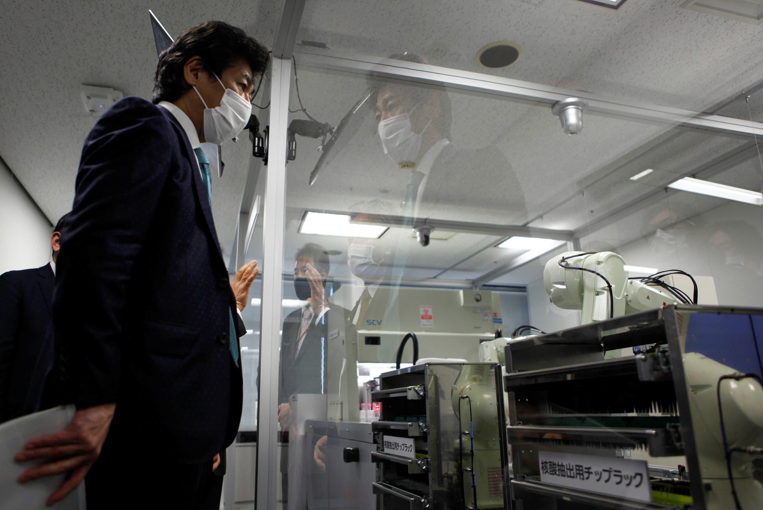 وزير الصحة الياباني نوريهيسا تامورا يعاين الروبوت الجديد