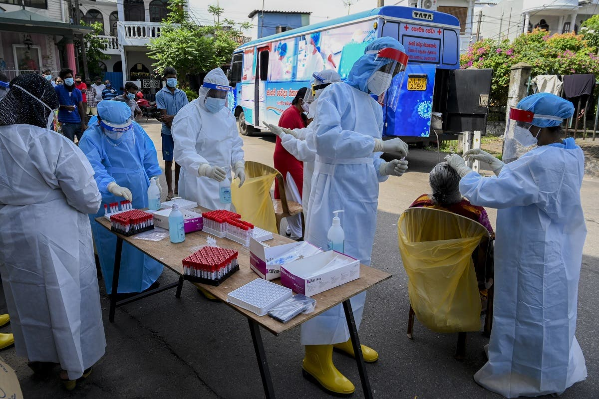 Health workers collect a swab sample from a resident to test for the COVID-19 coronavirus in Colombo, Sri Lanka on January 4, 2021. (Ishara S. Kodikara/AFP)