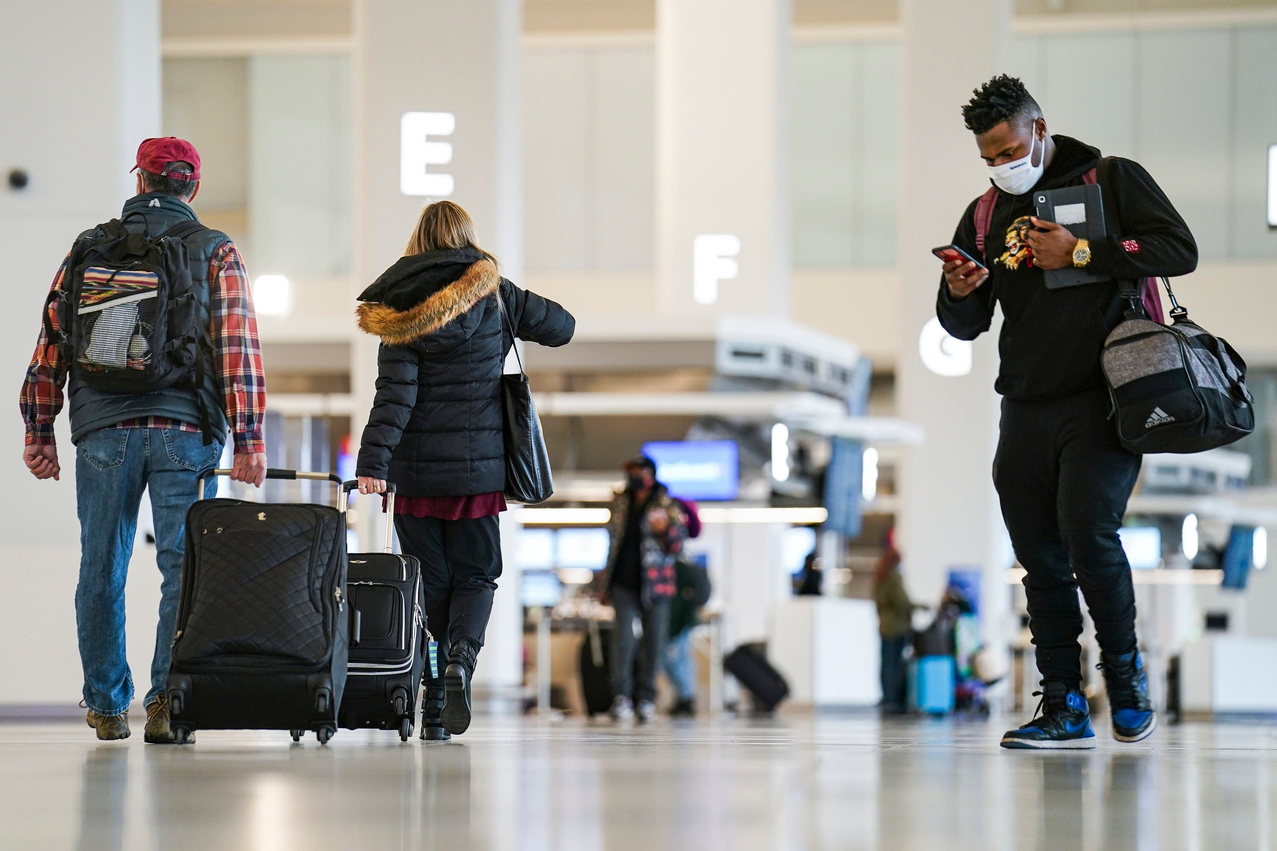 Travelers wearing protective masks to prevent the spread of COVID-19 arrive in Terminal C at LaGuardia Airport. (AP)