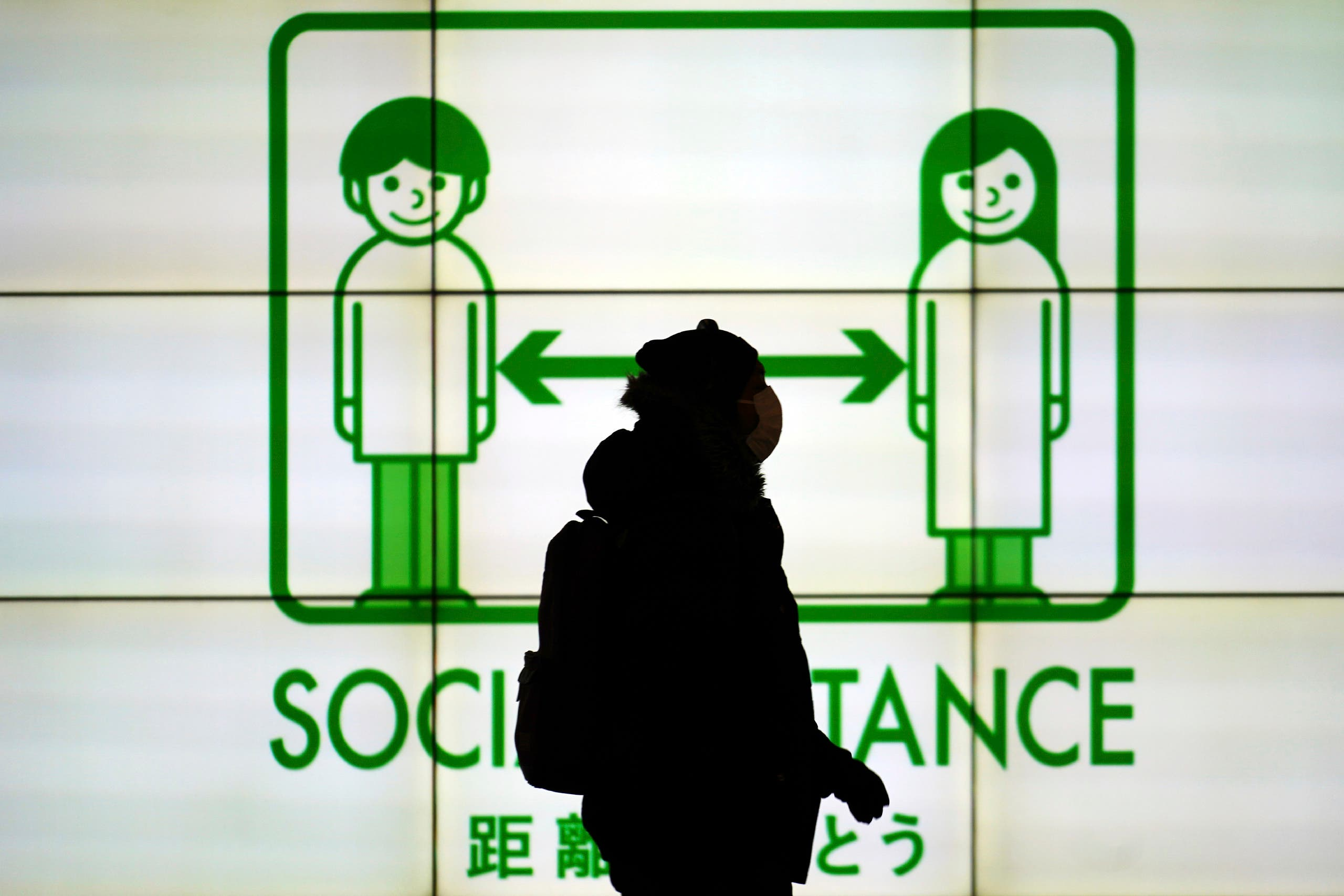 A woman wearing a protective mask to help curb the spread of the coronavirus walks in front of social distancing notice in Tokyo Tuesday, Jan. 19, 2021. (AP)