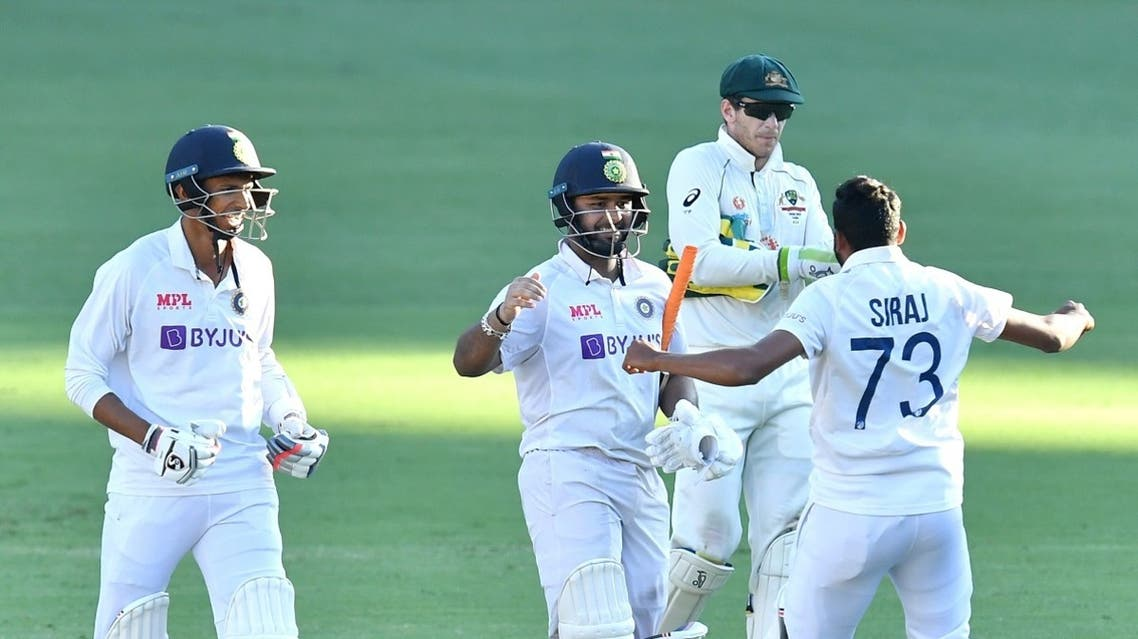 Rishabh Pant of India celebrates with teammates Navdeep Saini and Mohammed Siraj past Australia's captain Tim Paine after winning on day five of the fourth test match between Australia and India at the Gabba in Brisbane, Australia, on January 19, 2021. (Reuters)