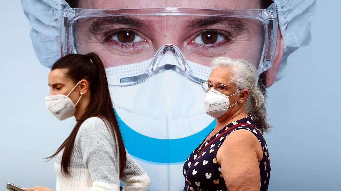 People, wearing protective face masks, walk past a dental clinic advertisement at Vallecas neighbourhood in Madrid, Spain, on September 18, 2020. (Reuters)