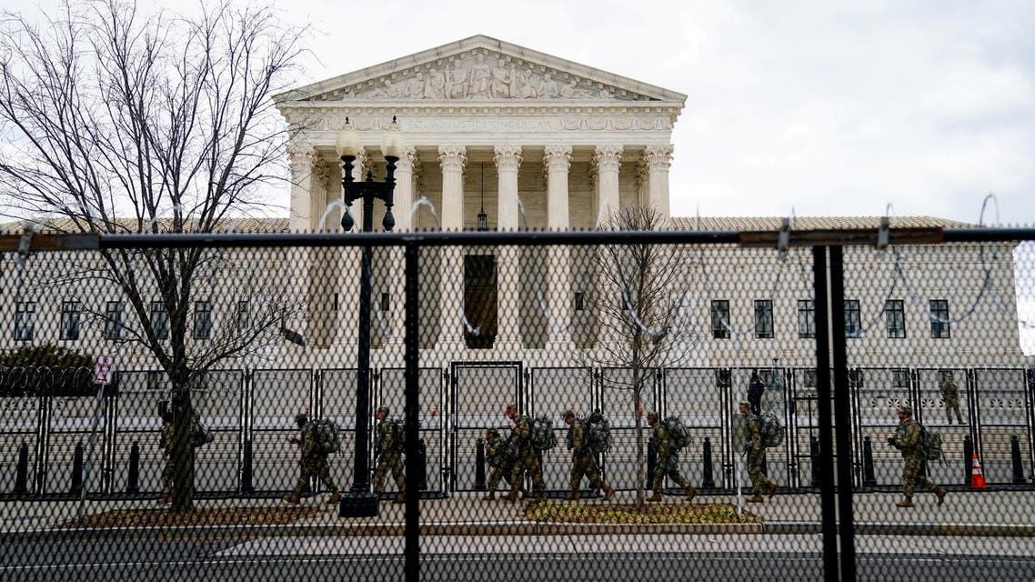 FILE PHOTO: National Guard troops walk behind fencing in front of the U.S. Supreme Court as security tightens ahead of presidential inaugural events on Capitol Hill in Washington, U.S., January 17, 2021. REUTERS/Erin Scott/File Photo