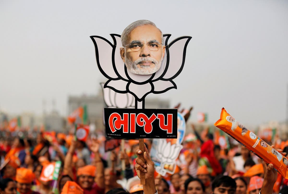 A supporter holds up a cut-out of a lotus, the election symbol of India's ruling Bharatiya Janata party with an image of Prime Minister Narendra Modi, in Kalol, Ahmedabad, India, December 8, 2017. (Reuters/Amit Dave)