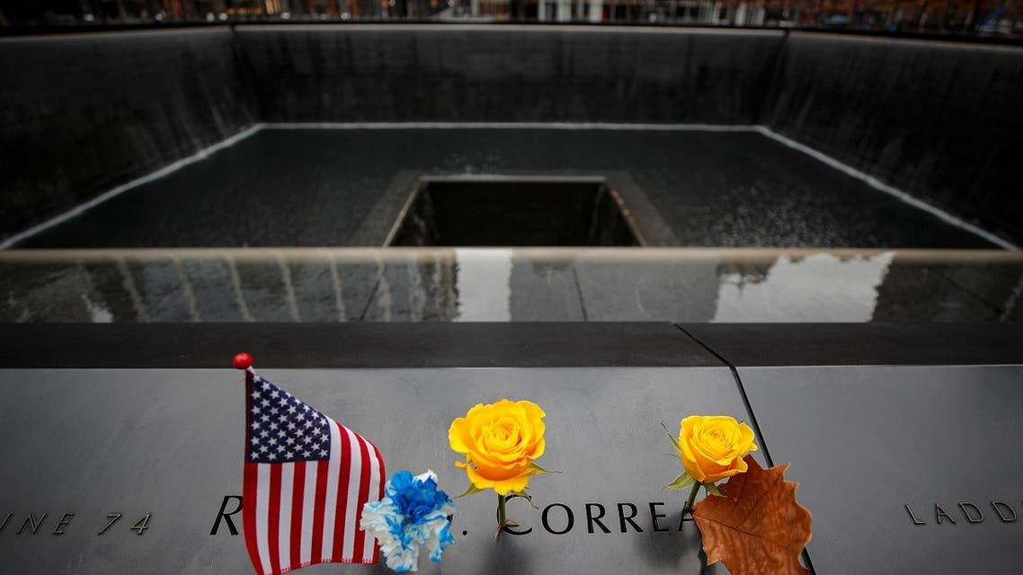 A flag and yellow rose are placed on an inscribed name of a veteran at the 9/11 Memorial during Veterans Day in New York. (Reuters)