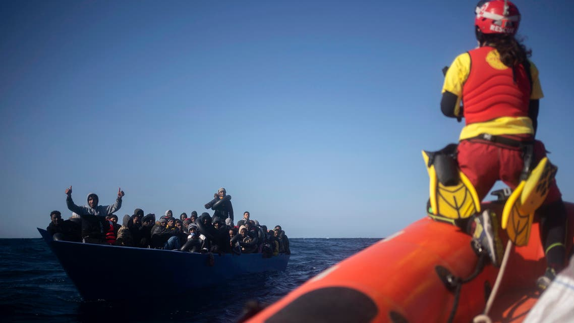 Migrants from Eritrea, Egypt, Syria and Sudan, are assisted by aid workers of the Spanish NGO Open Arms, after fleeing Libya on board a precarious wooden boat in the Mediterranean sea, about 110 miles north of Libya, on Jan. 2, 2021. (AP)