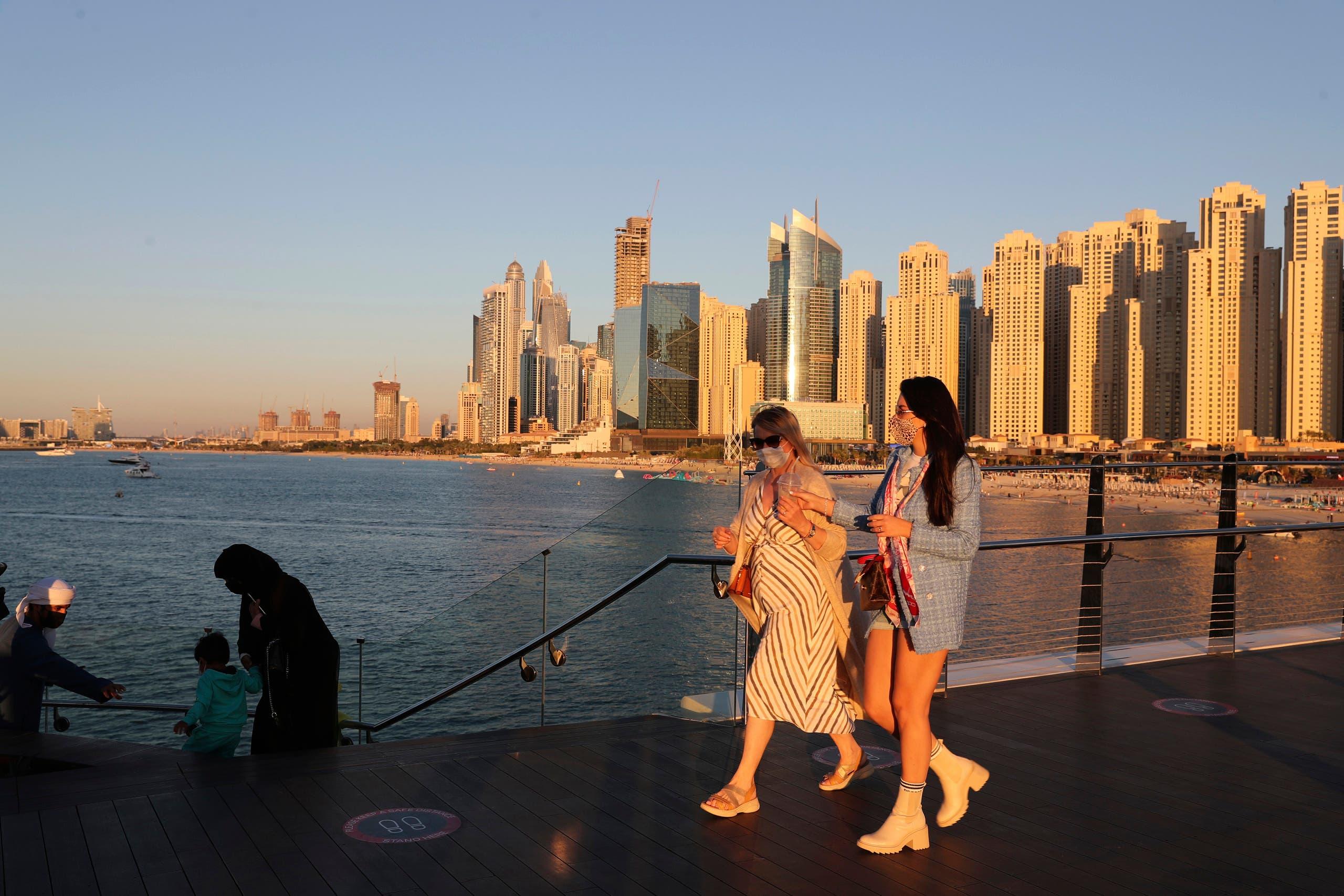 Tourists walk by an Emirati family in Dubai on Jan. 12, 2021. (AP)