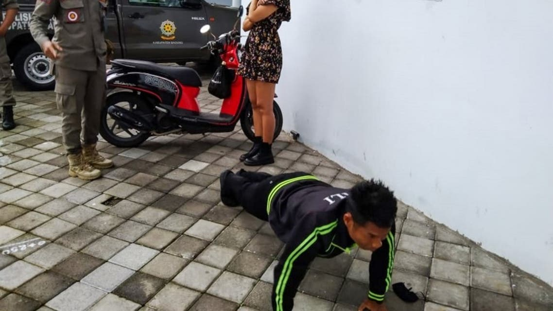 An undated handout picture released on January 20, 2021 by Bali's provincial public order agency shows an official looking on while a man performs push-ups as punishment for not wearing or improperly wearing face masks in Bali. (AFP)