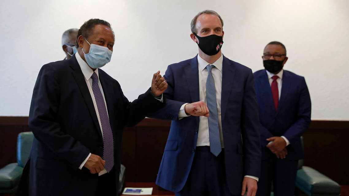 Sudanese Prime MInister Abdullah Hamdok, right, bumps elbows with British Foreign Secretary, Dominic Raab in the Cabinet Building, in Khartoum, Sudan on Jan. 21, 2021. (AP)