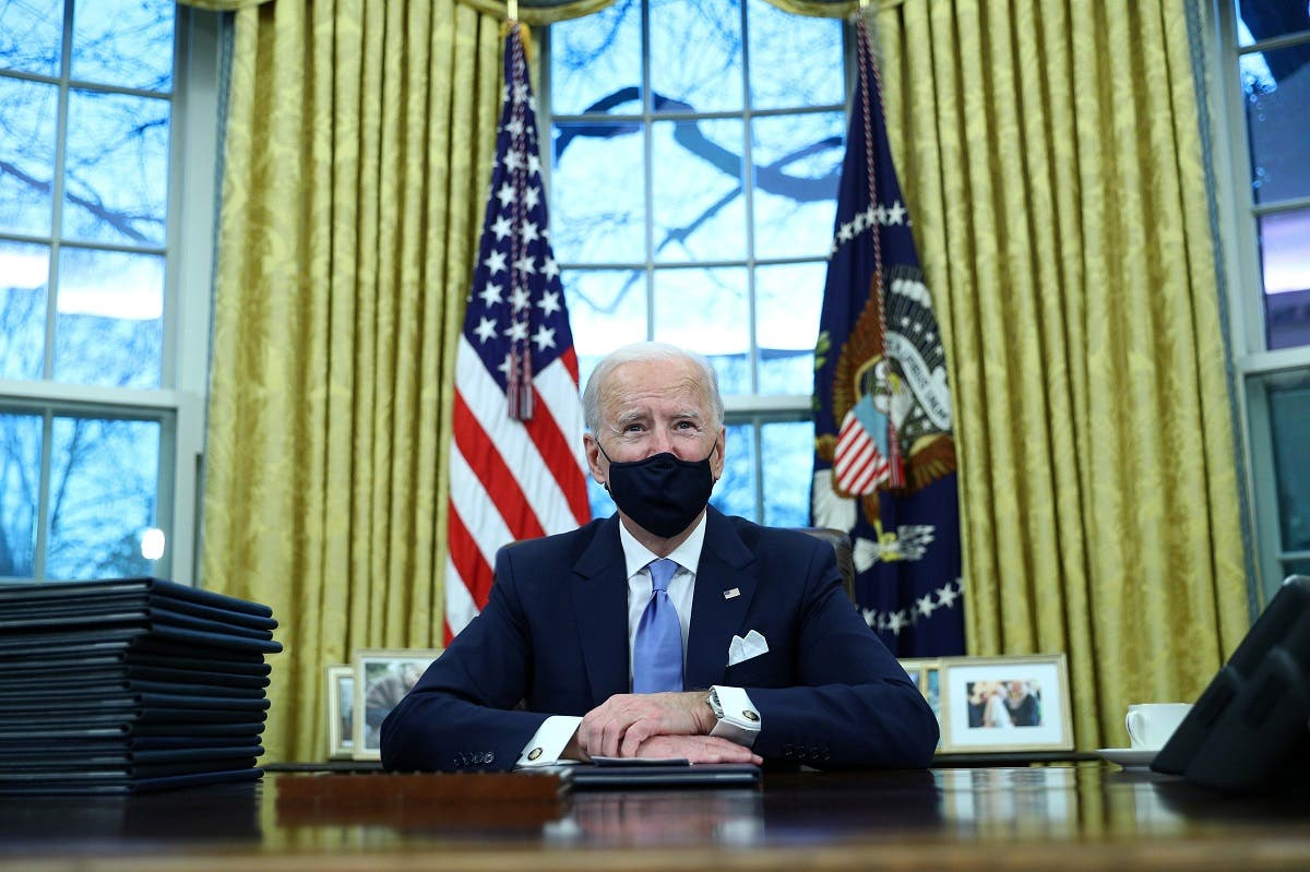 US President Joe Biden wearing a protective face mask signs executive orders in the Oval Office of the White House in Washington, Jan. 20, 2021. (Reuters)