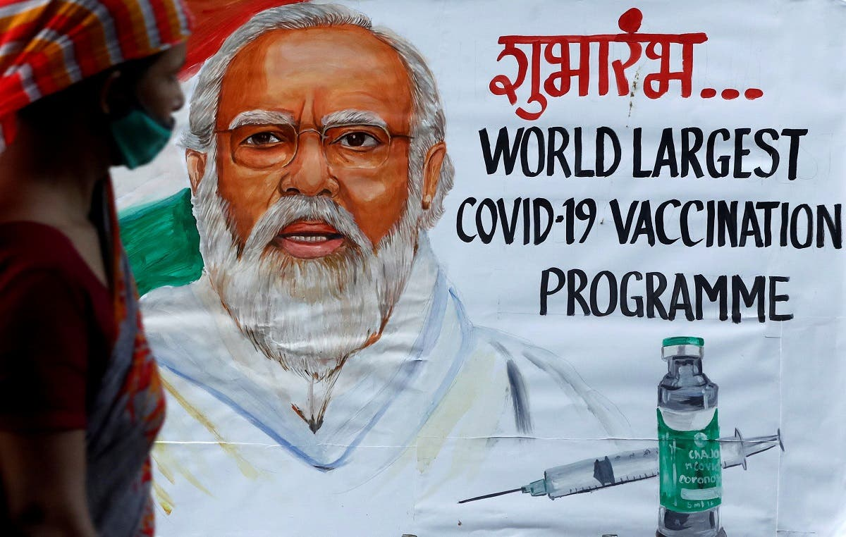 A woman walks past a painting of Indian Prime Minister Narendra Modi a day before the inauguration of the COVID-19 vaccination drive on a street in Mumbai, India, on January 15, 2021. (Reuters)