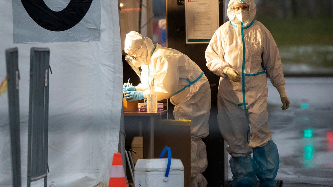 Medical workers prepare to take swab samples testing for the coronavirus, at a mobile coronavirus test station in Vilnius, Lithuania. (AP)