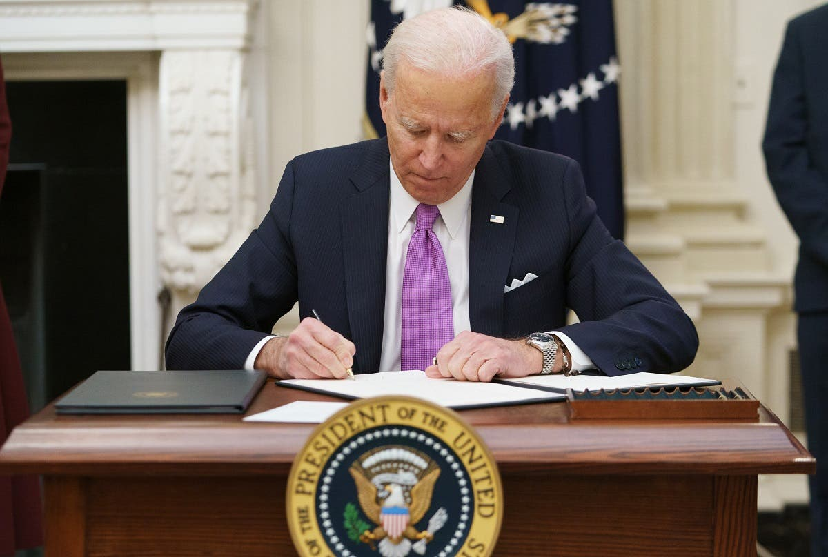 US President Joe Biden signs executive orders as part of the Covid-19 response in the State Dining Room of the White House, Jan. 21, 2021. (AFP)