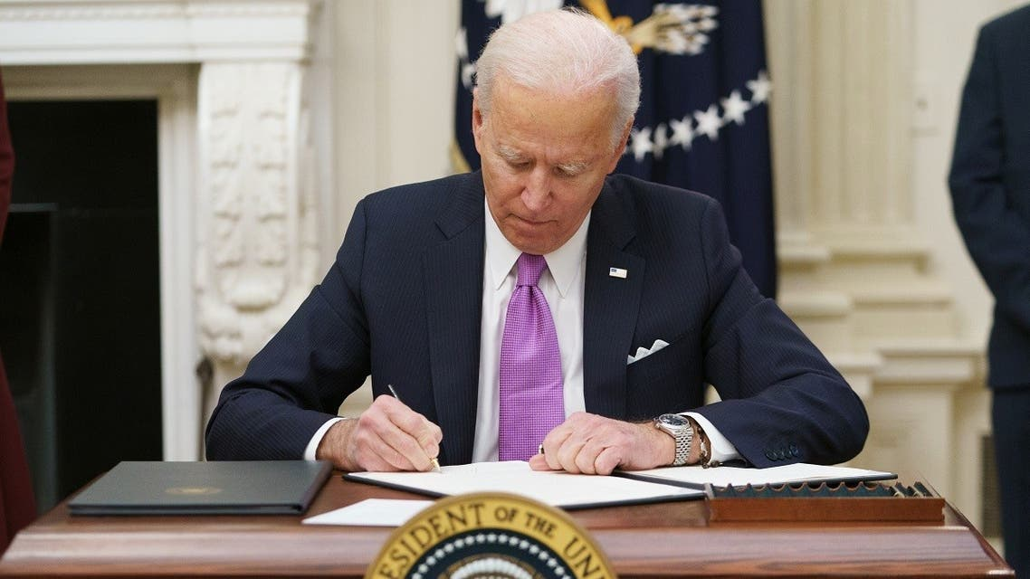 US President Joe Biden signs executive orders as part of the Covid-19 response in the State Dining Room of the White House, January 21, 2021. (AFP)
