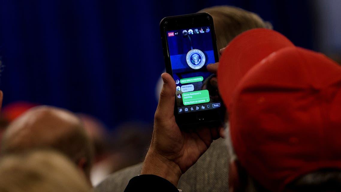 أحد أنصار ترمب يستمع إلى خطابه عبر بث على فيسبوك (أرشيفية- فرانس برس)