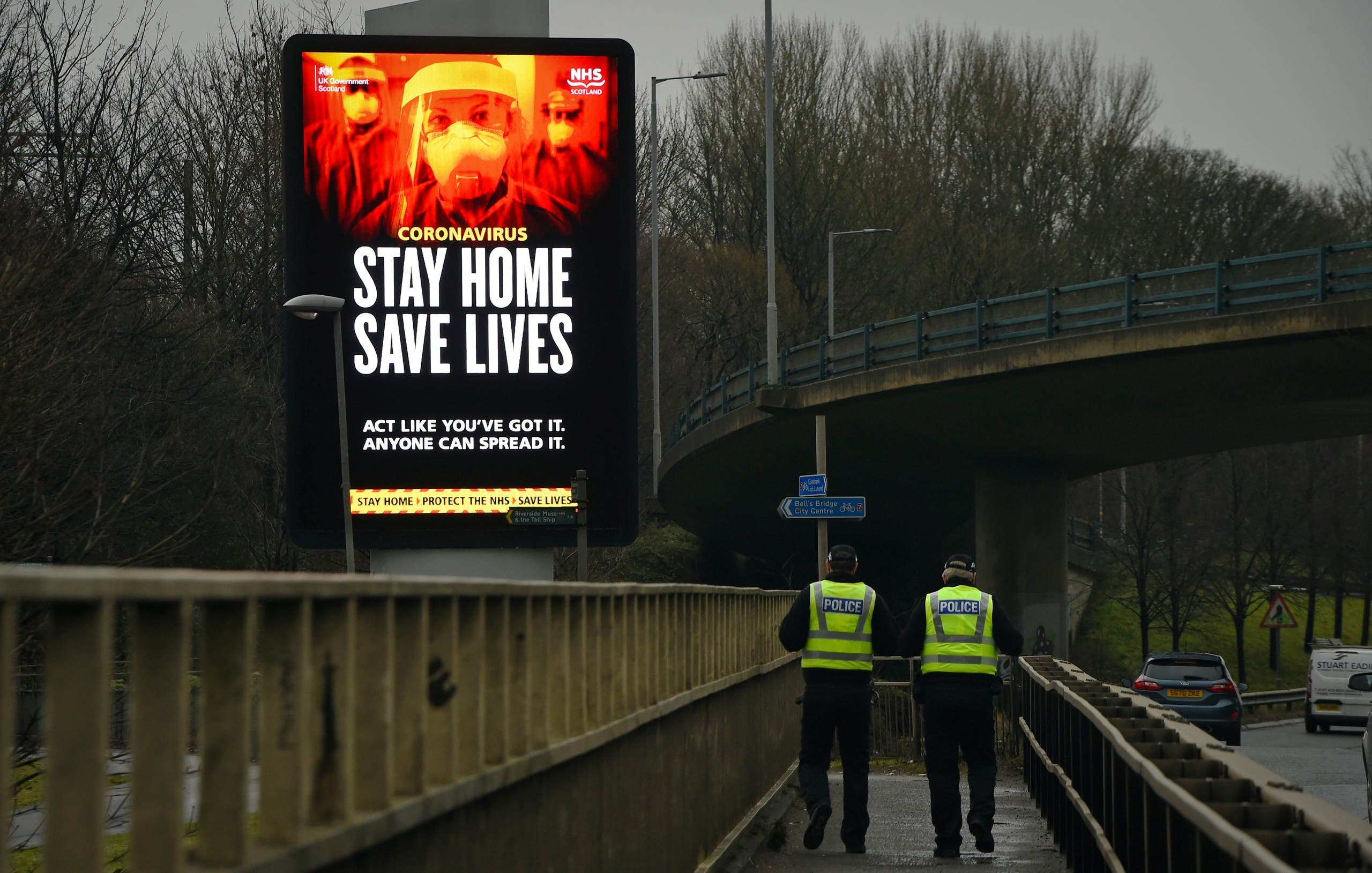 Police officers walk past a Covid-19 information board alongside the Clydeside Expressway in Glasgow, UK. (AFP)