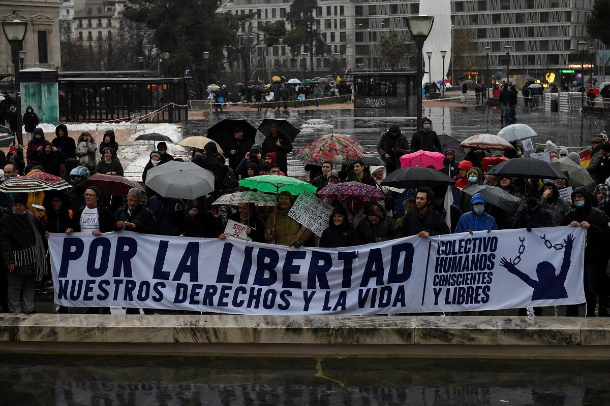 "Demonstrators hold a banner reading ""For the freedom of our rights and life"" during a protest against coronavirus restrictions in Madrid on January 23, 2021. (Pierre-Philippe Marcou/AFP)"