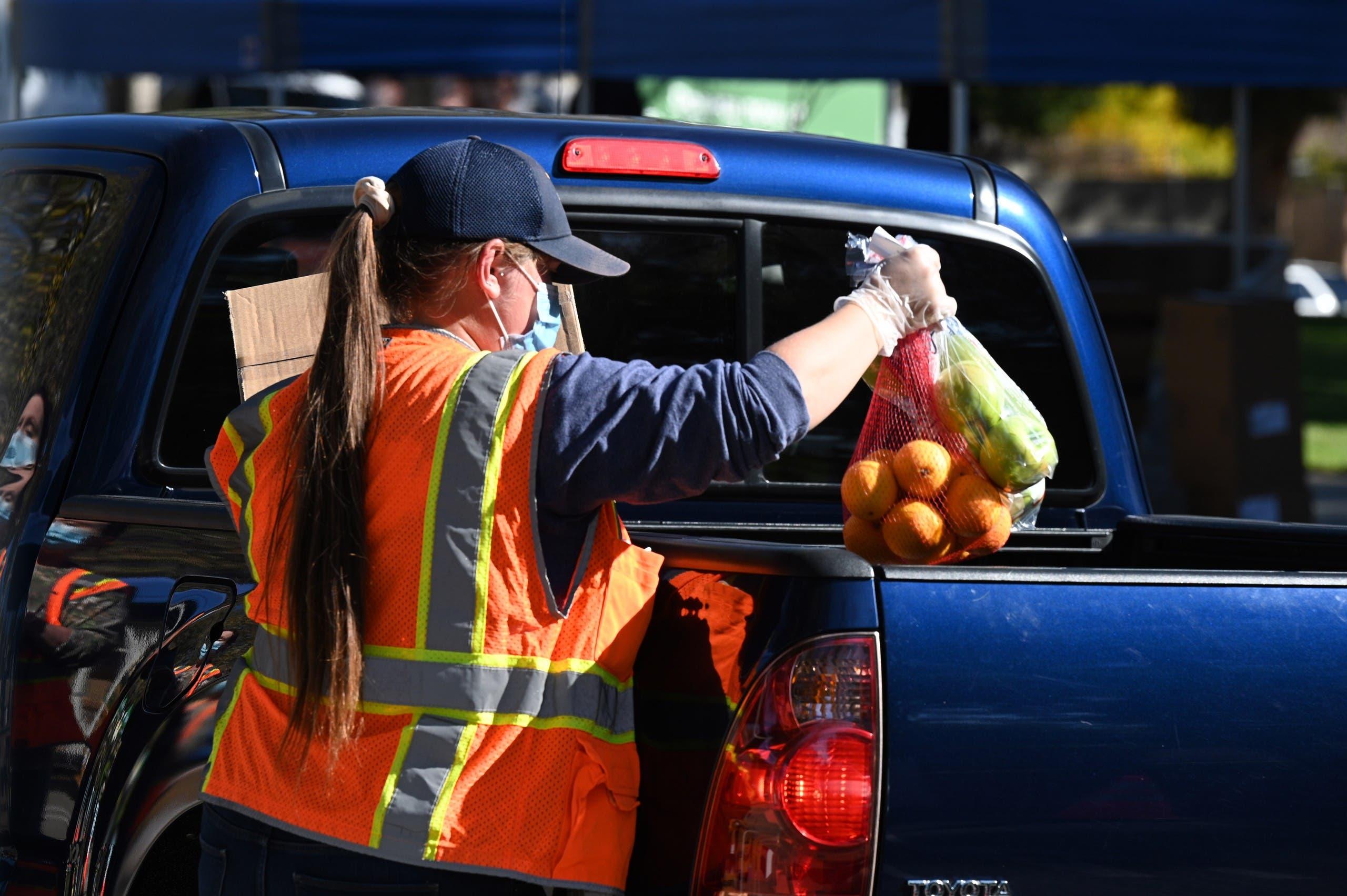 داوطلبان در تاریخ 1 دسامبر سال 2020 در لس آنجلس مواد غذایی را برای افراد ناامن توزیع می کنند