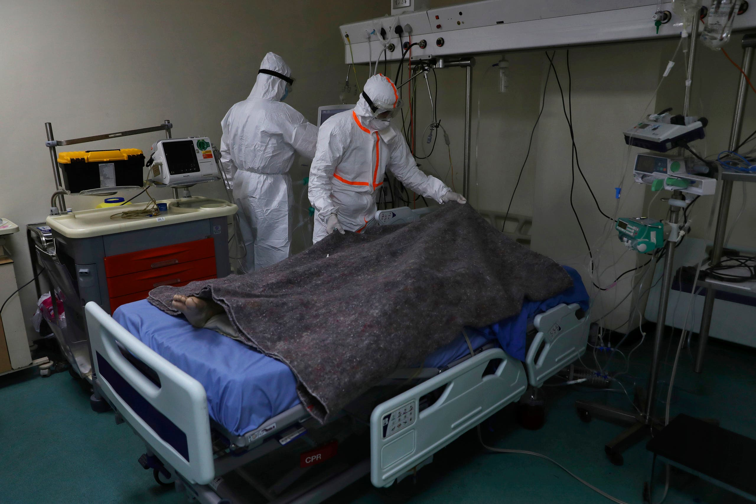 A medical staff covers with a blanket the body of a 35-year-old woman infected with COVID-19, at the intensive care unit of the Rafik Hariri University Hospital in Beirut, Lebanon. (AP)
