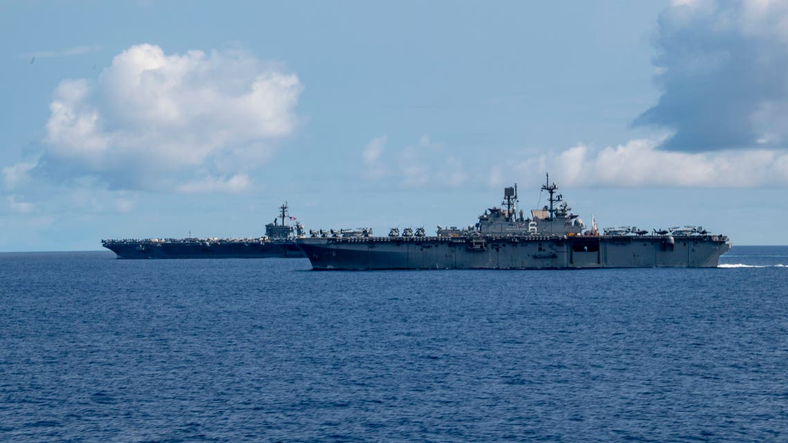 This US Navy handout photo obtained April 1, 2020 shows the Nimit-class aircraft carrier USS Theodore Roosevelt (CVN 71) and the America-class amphibious assault ship USS America (LHA 6) as they transit the Philippine Sea on March 24, 2020. The captain of the US nuclear-powered aircraft carrier Theodore Roosevelt told the Pentagon that new coronavirus is spreading uncontrollably through his ship and called for immediate help to quarantine its crew. But Defense Secretary Mark Esper on March 31, 2020 ruled out evacuating the ship, whose plight bears similarities to that on civilian cruise ships where the COVID-19 illness spread.