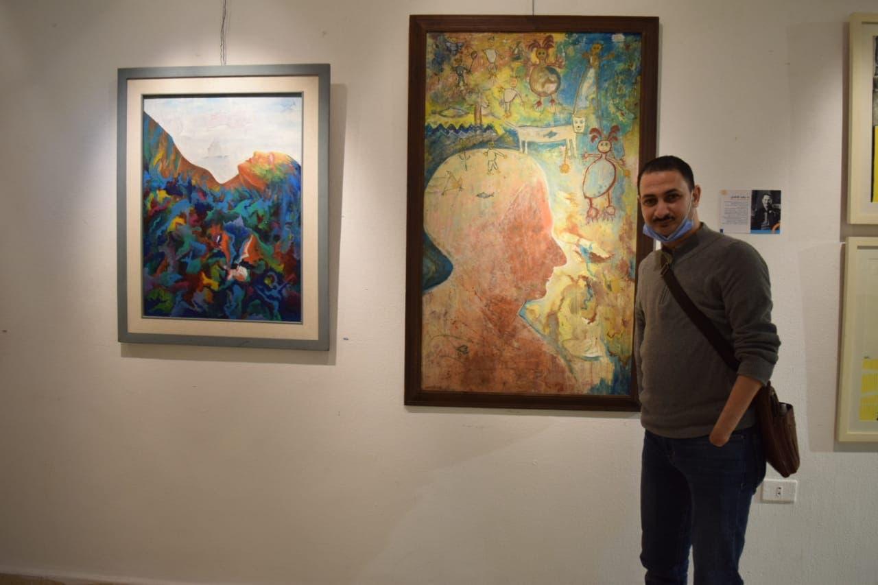 الفنان رضا فضل بجانب لوحاته