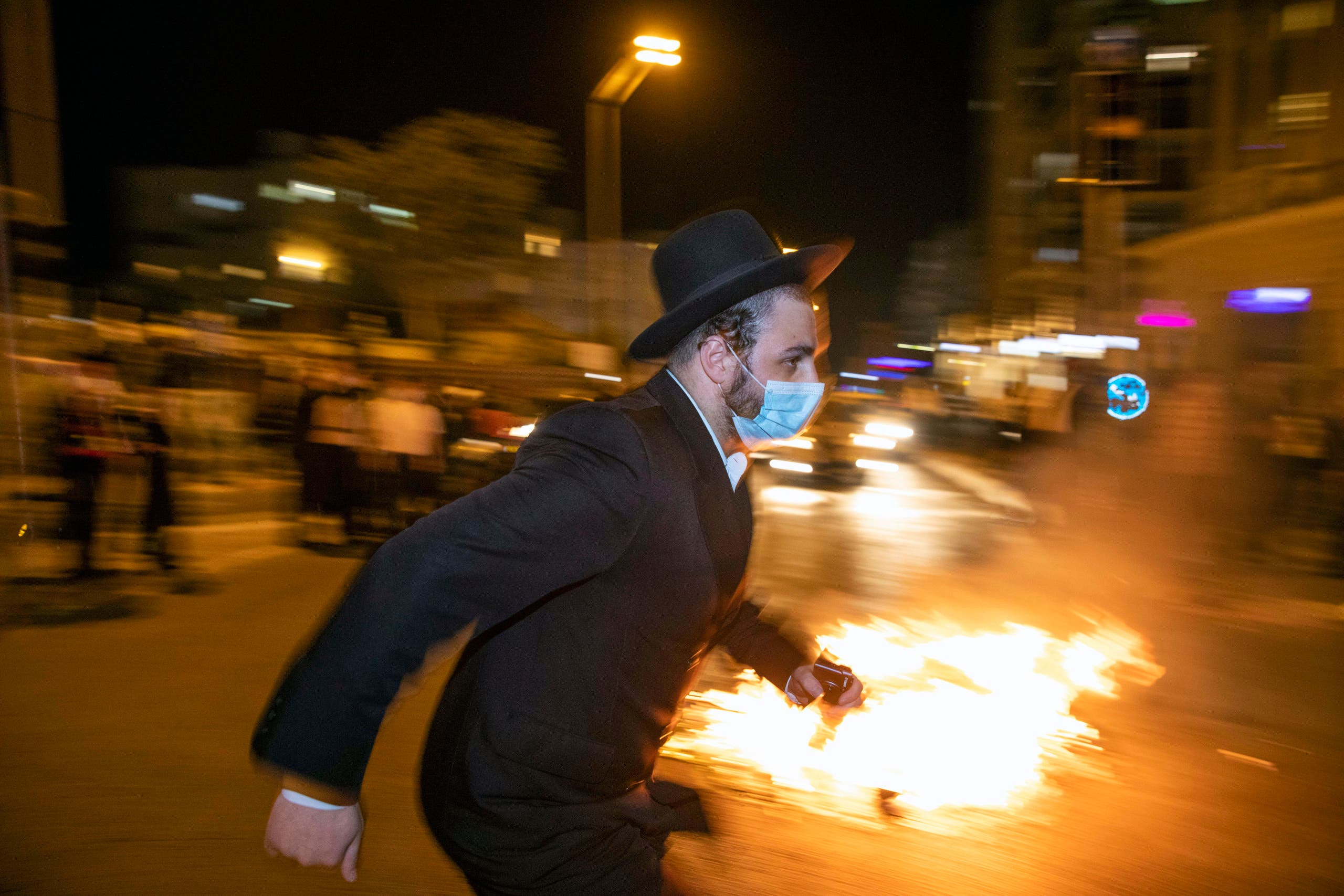 An Ultra-Orthodox Jewish man runs during a protest against lockdown put in place due to a coronavirus outbreak, in Jerusalem, Monday, July 13, 2020. (AP)