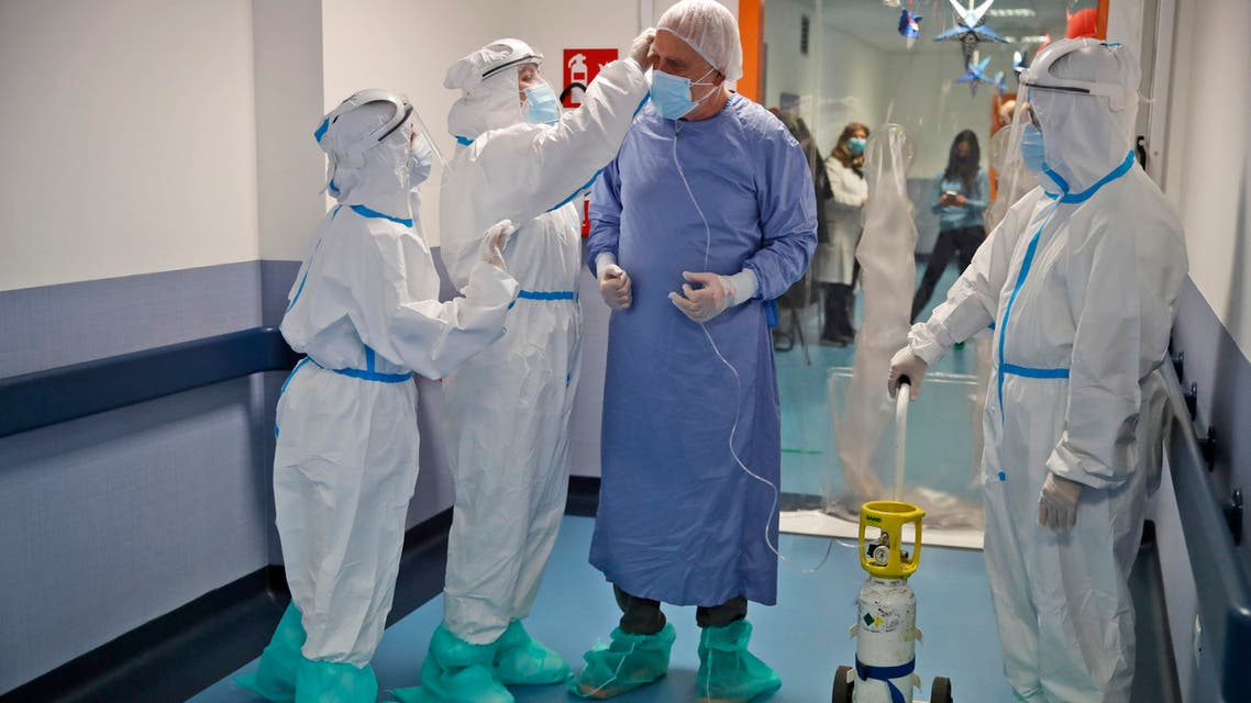 Giancarlo Vannimartini, an anesthetist who has been hospitalized for 10 days, is helped by medical personnel in the COVID-19 ward of the Ospedale dei Castelli Hospital in Ariccia, near Rome on Jan. 20, 2021. (AP)