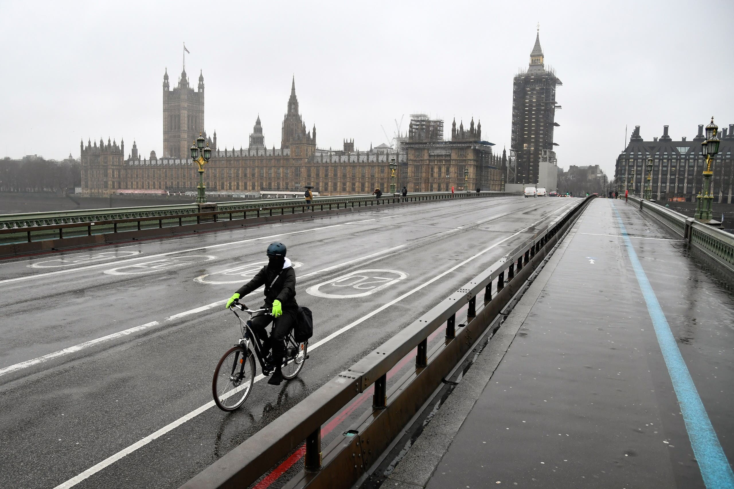 A cyclist rides across the deserted Westminster Bridge, amidst the current lockdown restrictions, as the spread of the coronavirus disease (COVID-19) continues, in London, Britain. (Reuters)